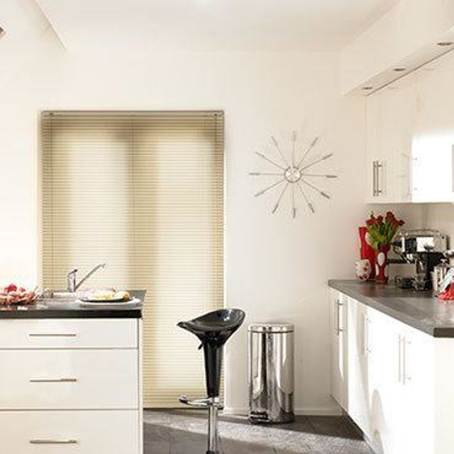 Light wood Aluwood Elderberry Venetian blinds hung in a modern kitchen
