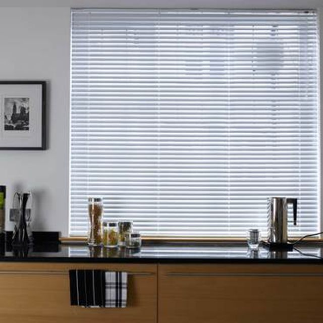 Light wood Portfolio Classic White Venetian blinds hung in a kitchen window