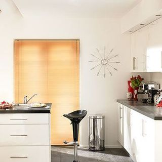 Light wood Portfolio Ivory Venetian blinds hung in a modern kitchen
