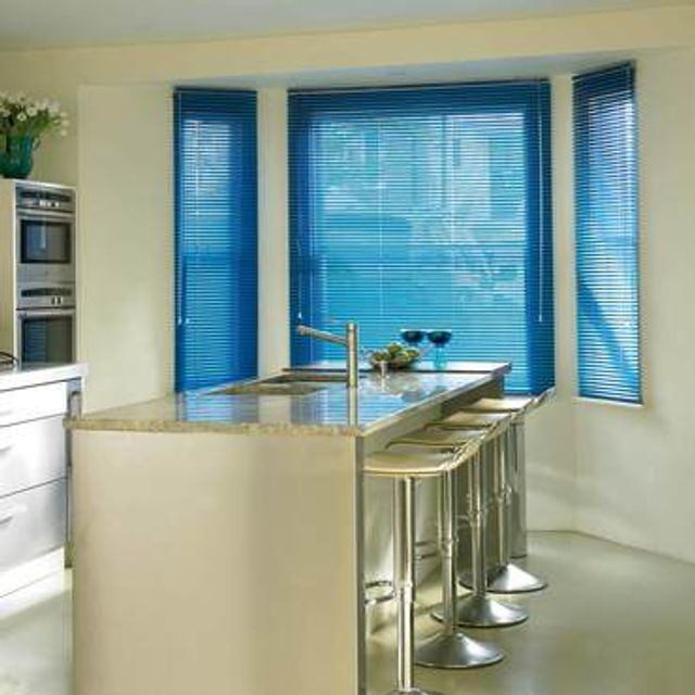 Bright blue Portfolio Sapphire Venetian blinds hanging in a kitchen window