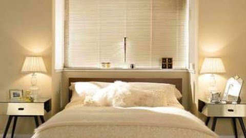 Venetian blinds decorated in Spectrum Magnolia fitted to a rectangular window in a bedroom decorated in cream