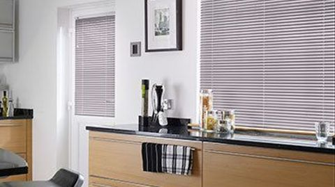 Light pink venetian blinds fitted to a large kitchen window and door window in a kitchen decorated in white with wood kitchen units