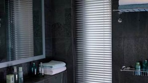 Silver venetian blind attached to a tall rectangular window in a bathroom decorated with dark slate tiles