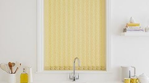 Yellow vertical blinds fitted to a tall rectangular window in a kitchen decorated in white