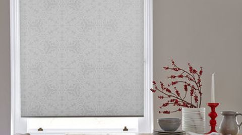 Silver coloured roller blind with a repeating pattern in a slightly darker shade attached to a tall rectangular window in a dining room that is decorated with beige walls and red blossom on the kitchen table