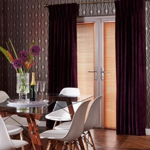 Dining room with glass table and glass door perfectly fitted with Gold Copper venetian blinds and Made To Measure Lyon Plum curtains