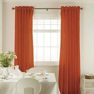 Tetbury Orange Curtains in dining room with white furniture