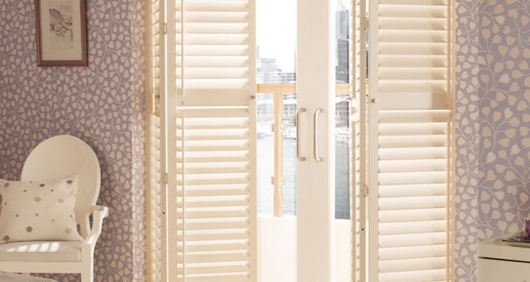Tracked White Shutters in a Bedroom