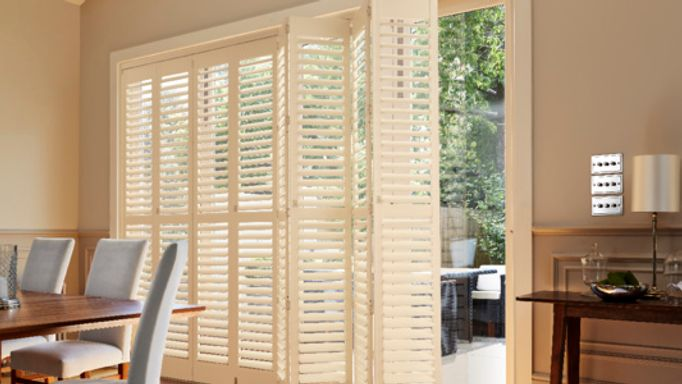 White tier-on-tier full height shutters on patio door dining room