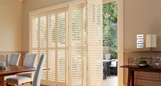 White tier-on-tier full height shutters on patio door dining room -