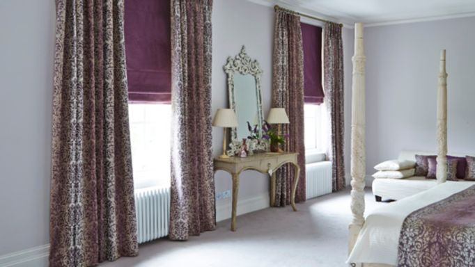 Patterned Curtains with Purple Roman blinds in guest bedroom