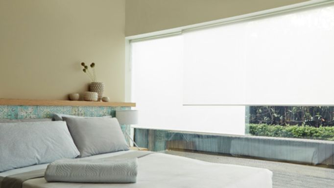 White bedroom Roller blind in a wide window