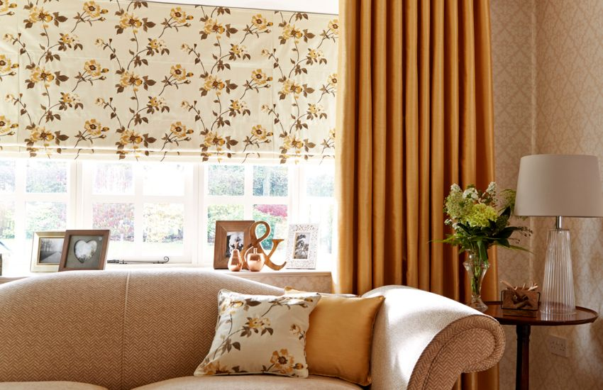 floral decorated roman blinds paired with orange curtains in a living room decorated in neutral colours