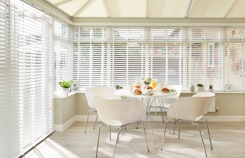 White faux wood blinds in a conservatory with a table set for breakfast