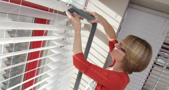 Clean wooden blinds with a vacuum cleaner -