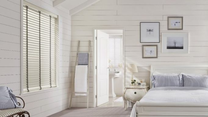 White wooden blinds in white bedroom