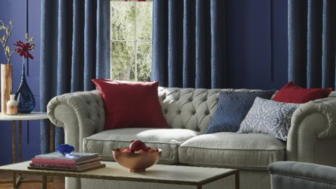 Chesterfield sofa with blue curtains in living room