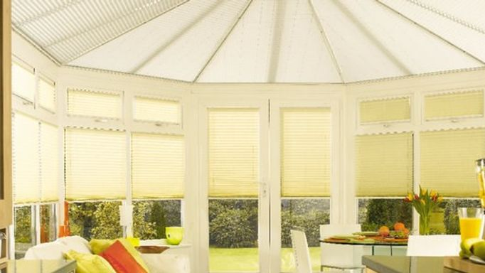 white conservatory roof blinds in a yellow shaded conseravtory