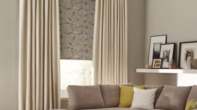 Cream curtains and beige patterned roller blind