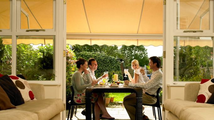 Yellow Awning Used to Extend Conservatory - Family enjoying alfresco dining with a yellow awning
