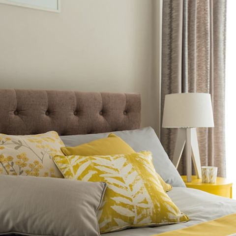 Selection of yellow print floral fabric cushions on a bed in a bedroom
