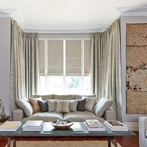 Cream roman blinds and cream textured curtains in a living room