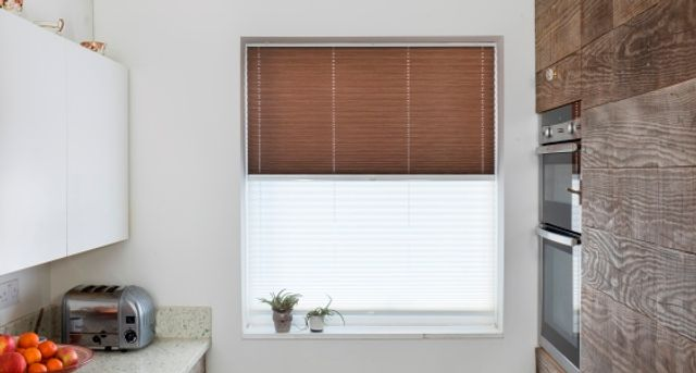 Brown venetian blinds paired with white transition blinds on a rectangular window in a kitchen decorated with white and wood tones